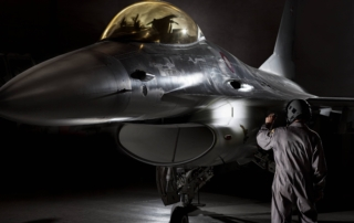 F16 fighter pilot inspecting his airplane with professional Suprabeam flashlight
