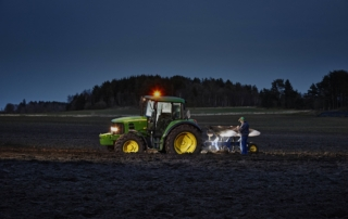 Professional farmer inspecting his John Deere tractor with the powerful Suprabeam Q7compact flashlight