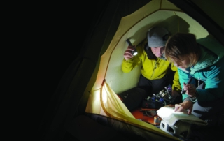 Hikers reading their map using flashlights