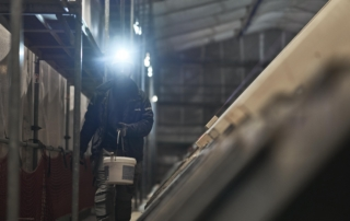 Electrician working on a construction site, with a S4 rechargeable headlamp mounted on his safety helmet