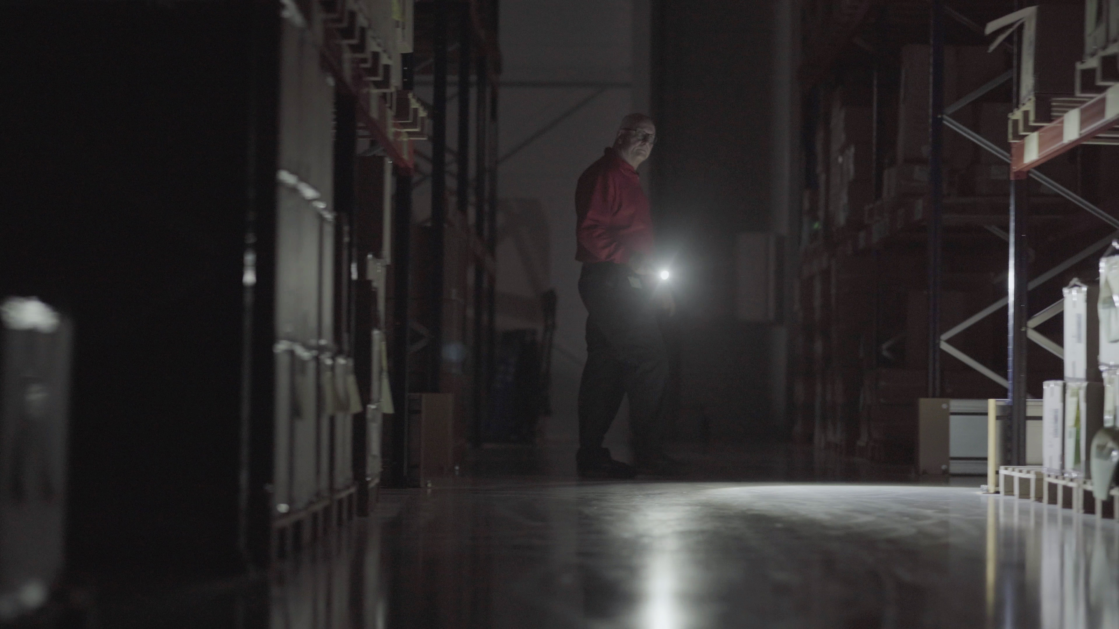 Security guard inspecting warehouse at night